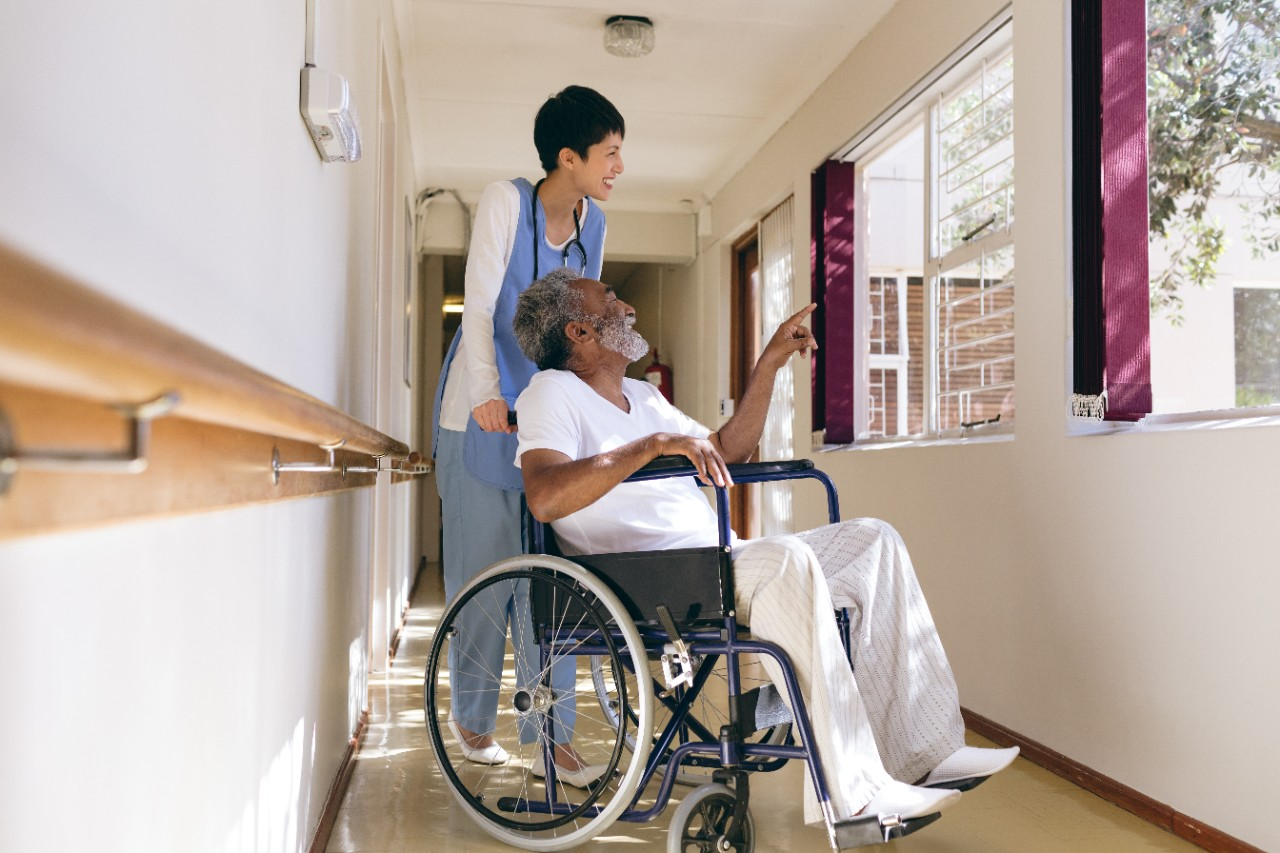Side view of  Asian female nurse and senior African-american male patient interacting with each other while standing in corridor at retirement home