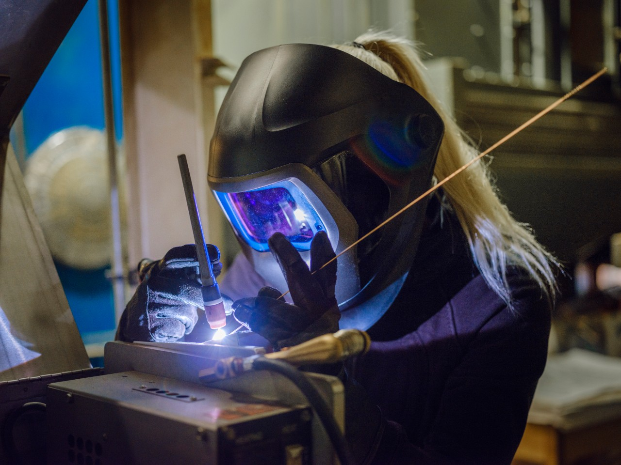 A woman tig welder works in a production facility to repair a piece of equipment.