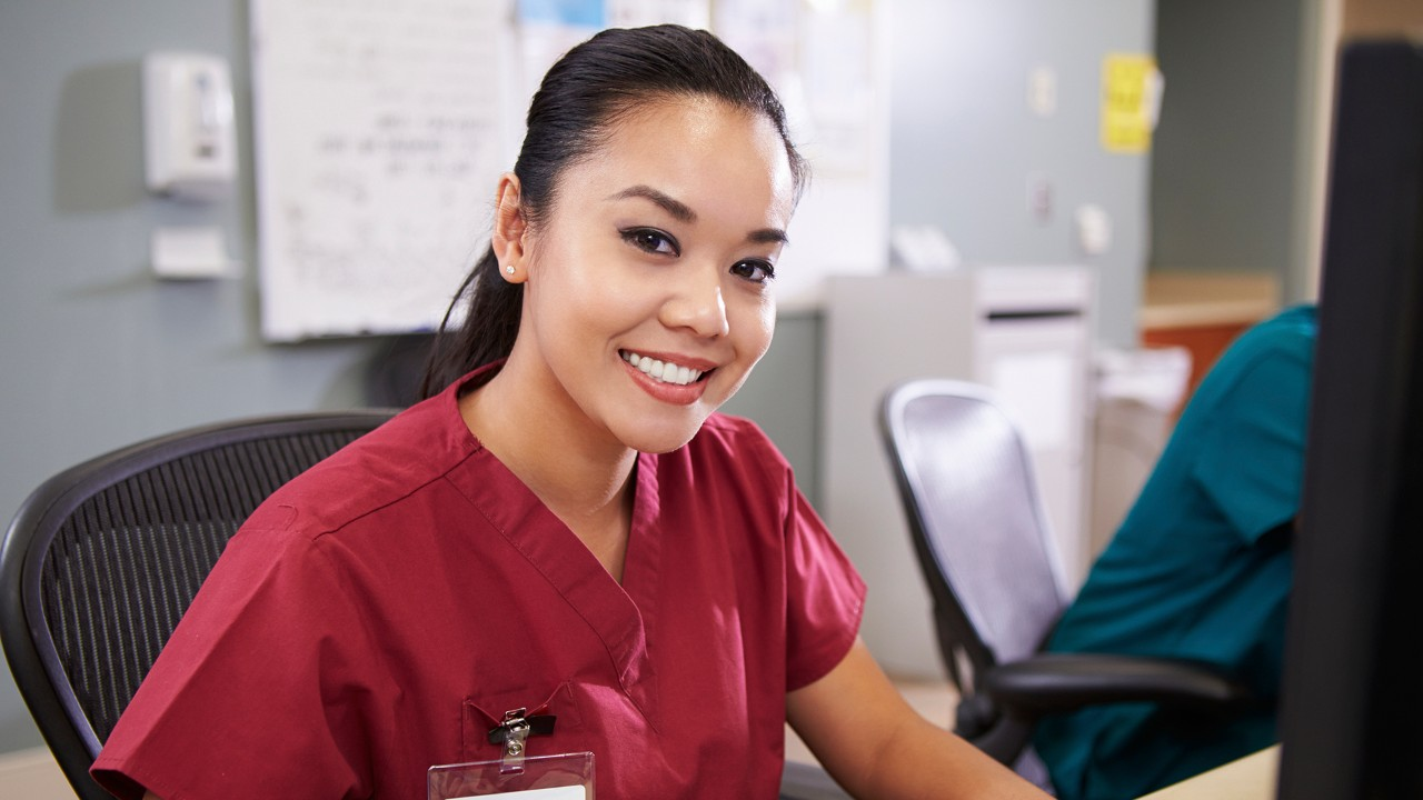 Portrait Of Female Nurse Working At Nurses Station